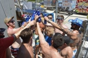 A group of guys at a bachelor party toasting on a boat