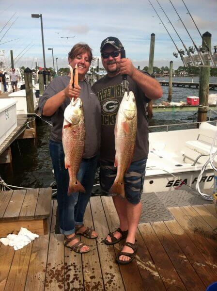 Couple Each Holding Redfish on Dock