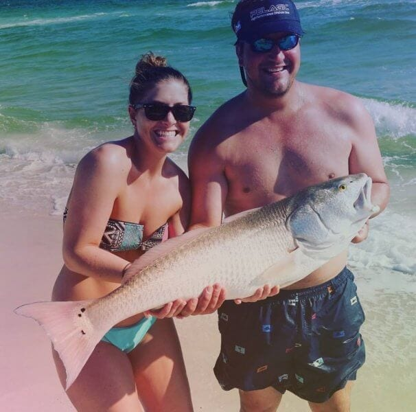 Couple lands monster redfish while fishing on the beach.
