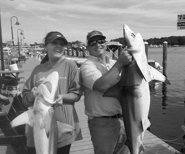 Two Guests Each Holding a Thrasher Shark