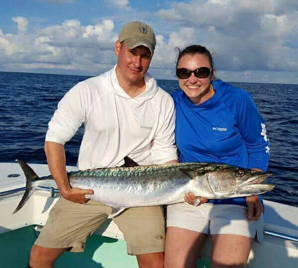 Guests Holding a King Mackerel They Caught During Their Extreme Swordfish Trip