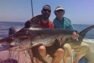 Men Holding Swordfish