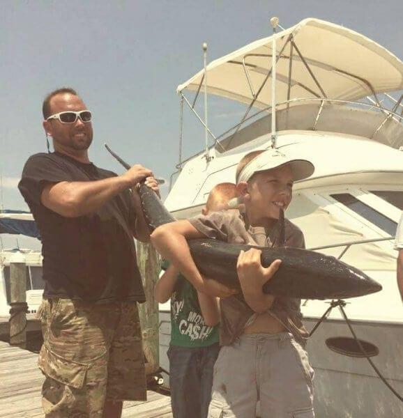 Family Holding Massive Tuna