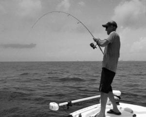 Man Catching Fish with Light Tackle at Front of Boat